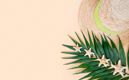 Straw hat, palm leaf and sea stars on neutral beige background. Summer travel and vacations concept. Top view, minimal flat lay, copy space 写真素材