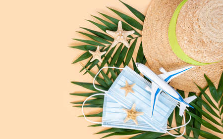 Summer hat, plane, medical mask and sea stars on palm leaf on neutral beige background. Travel and holiday restrictions during global coronavirus or Covid-19 pandemic. Top view, flat lay, copy space