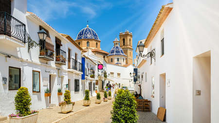 Street of Altea old town in Spain. Beautiful village with white houses and blue domed church Our Lady of Solace. Popular Spanish tourist destination, Costa Blanca region