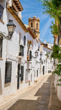 Typical street of Altea old town with white houses in Spain. Beautiful village with cobblestoned narrow streets, popular tourist destination in Costa Blanca region. Vertical orientation.