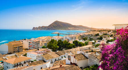 Altea, Spain - beautiful village with white houses, pink flowers, beach, harbour and mountains at sunset. Popular Spanish tourist destination in Costa Blanca region on Mediterranean sea