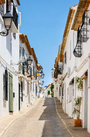 Typical view of Altea old town in Spain. Beautiful village with cobblestoned narrow streets, typical white houses and lanterns, popular tourist destination in Costa Blanca region. Vertical orientation