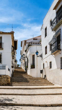 Altea old town, Spain. Beautiful village with cobblestoned narrow step street, typical Mediterranean white houses and lanterns, popular tourist destination in Costa Blanca. Vertical orientation