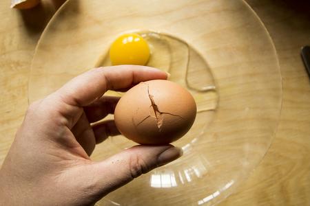 hand cracking farm eggs