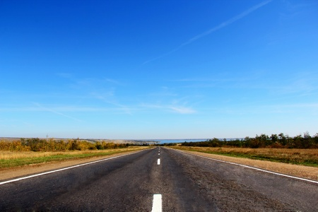 lane lines: Summer landscape with line of road and blue sky Stock Photo