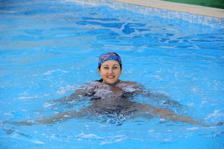 Beautiful young smiling girl sailling in pool in blue kerchief photo
