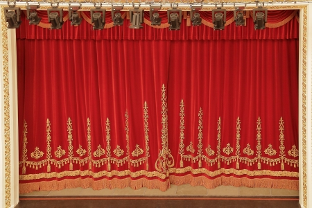 Theatrical red velvet curtain with gold pattern Stock Photo