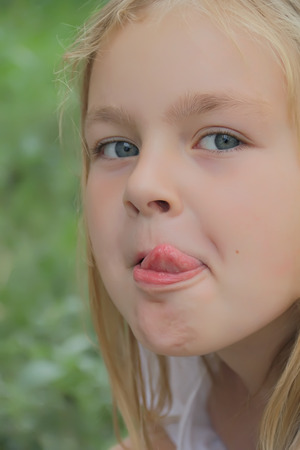 Portrait of beautiful girl with put out tongue photo