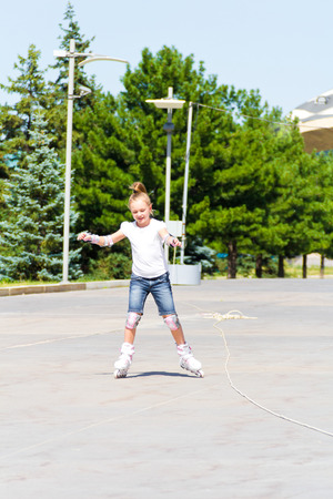 Photo of cute girl on roller skates in summer