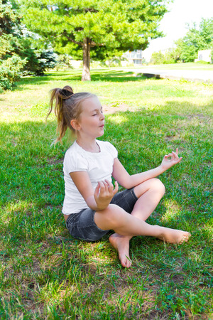 Cute girl are sitting on green grass in lotus pose