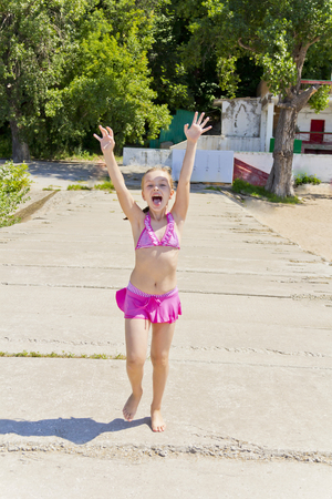 six girl: Photo of jumping girl on the riverbank in pink swimsuit Stock Photo