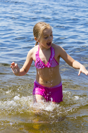 white girl: Cute girl in pink swimsuit bathing in the sea