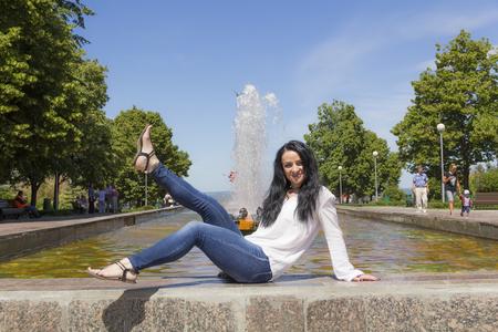 Caucasian brunette with upward legs on fountain background