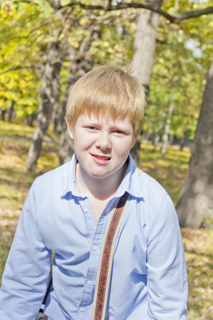 Cute blond boy in autumn yellow forest