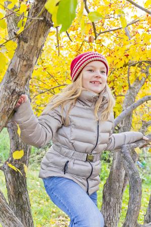 colegiala: Cute girl sitting on spreading tree in autumn