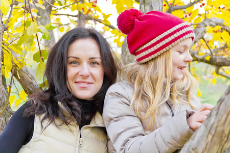 Portrait of happy mother and daughter in autumn