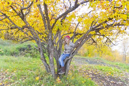 Cute girl sitting on spreading tree in autumn