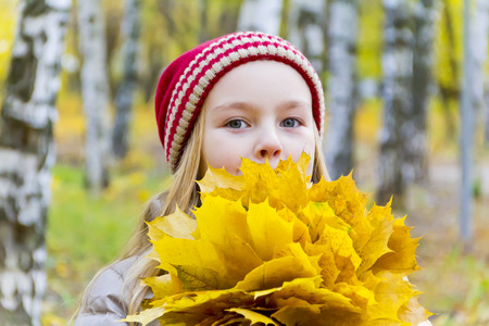 Photo of girl with bouquet from sheets in autumn