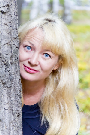 European blond woman with long hair on tree background