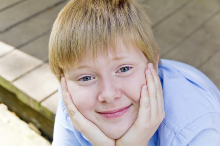 out door: Portrait of cute blond boy sitting out door