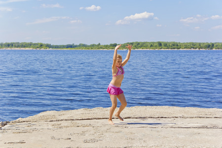 Dancing girl on the riverbank in pink swimsuit