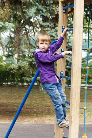 rope ladder: Cute boy climbing a rope ladder on the playground
