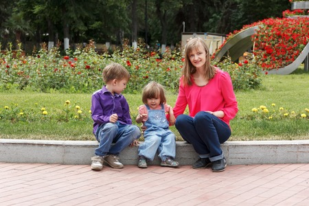 twenty two: Mother with boy and baby girl sitting in summer park