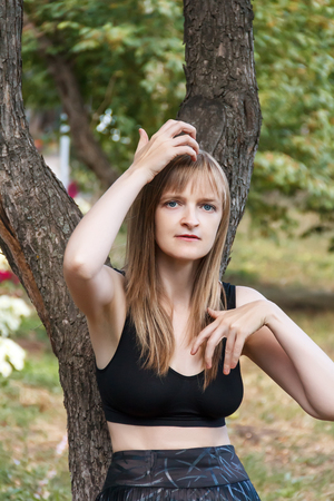 correcting: Blond woman correcting hairstyle near tree in summer