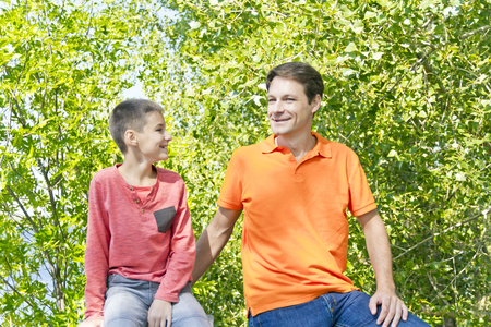 twenty thirteen: Father and son are talking smiling in summer park Stock Photo