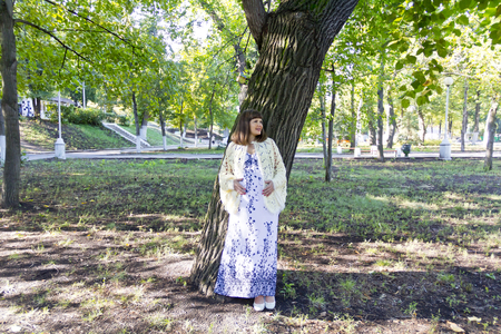 Pregnant woman with brown standing near tree in summer Stock Photo