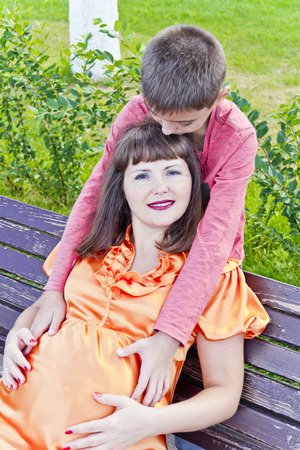 twenty thirteen: Pregnant mother sitting on the bench and son embrace her stomach Stock Photo
