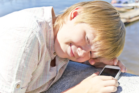 Blonde smiling boy with cellular phone in sunlight Stock Photo