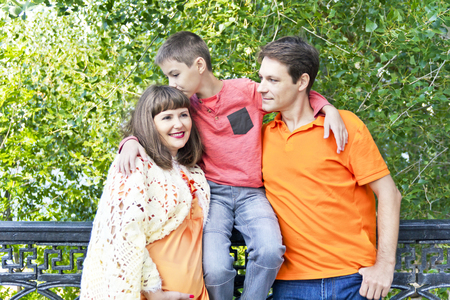 twenty thirteen: Happy family son kissing pregnant mother in summer embankment Stock Photo