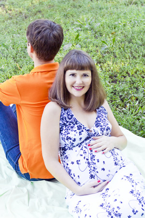 Pregnant wife support of husband back sitting on green grass