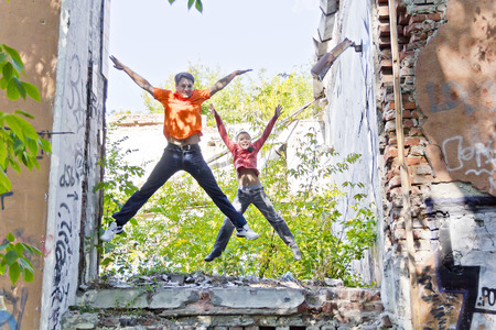 Father and son are jumping through ruins in summer day Stock Photo