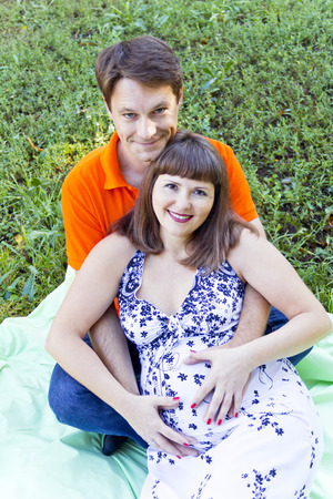 Husband and pregnant wife sitting on green grass in summer time Stock Photo
