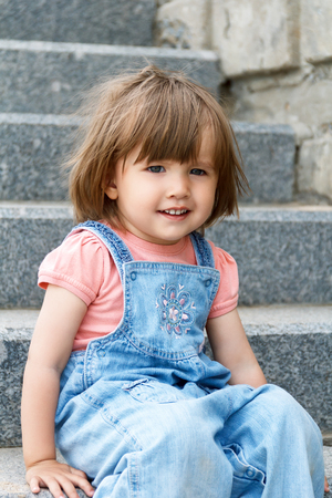 Baby girl in blue cloth sitting on the stone stairs