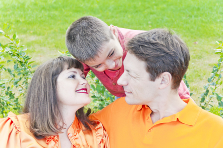 Talking family with mother father and son on green background Stock Photo