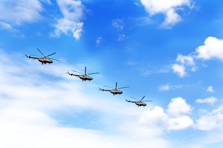 Parade of four war helicopters in the blue sky Stock Photo