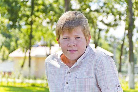 Portrait of  blond boy in a white shirt in green park Stock Photo