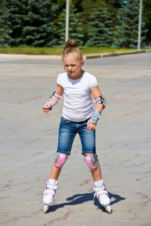 Learning girl on roller skates in summer Stock Photo