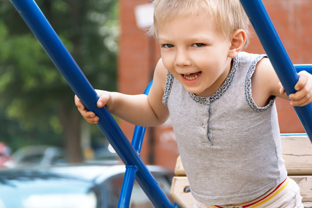 Blond boy with open mouth rides on seesaw Stock Photo