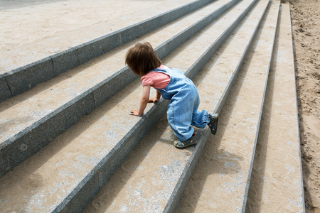 Baby girl in blue cloth creep up on the stairs Stock Photo