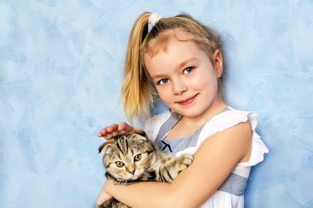 Blond girl with grey kitty on blue