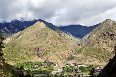 Picturesque landscape with a small village at the foot of mountains