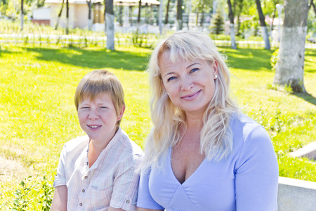 Happy blond woman and son smiling in the summer park