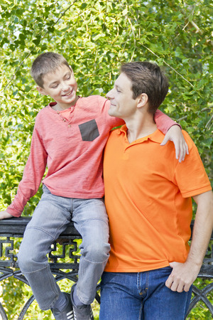 Father and son are talking smiling in summer park Stock Photo