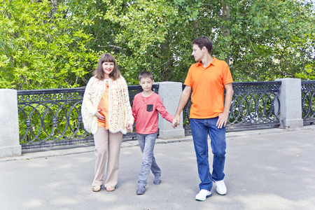 Walking family mother and son with father in summer embankment