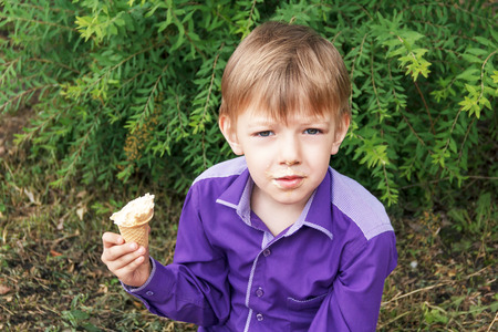Horizontal photo of blond boy are eating icecream in summer Stock Photo