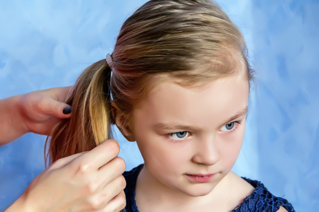 Mother makes hairstyle to daughter on blue